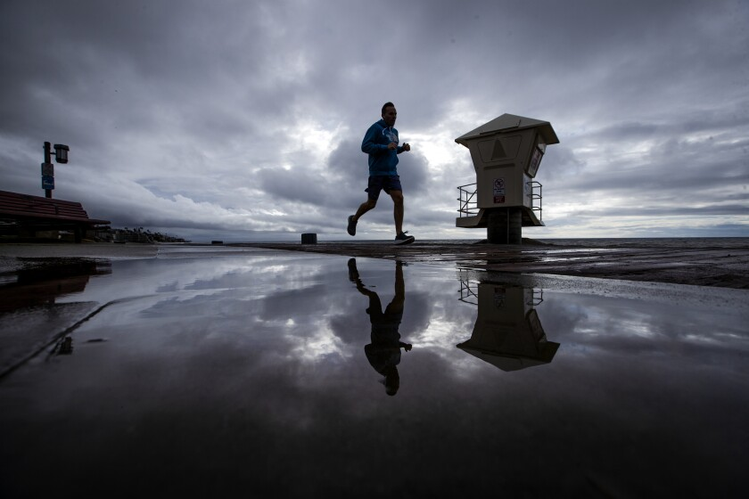 A man is reflected in a puddle at Main Beach in Laguna Beach this week.