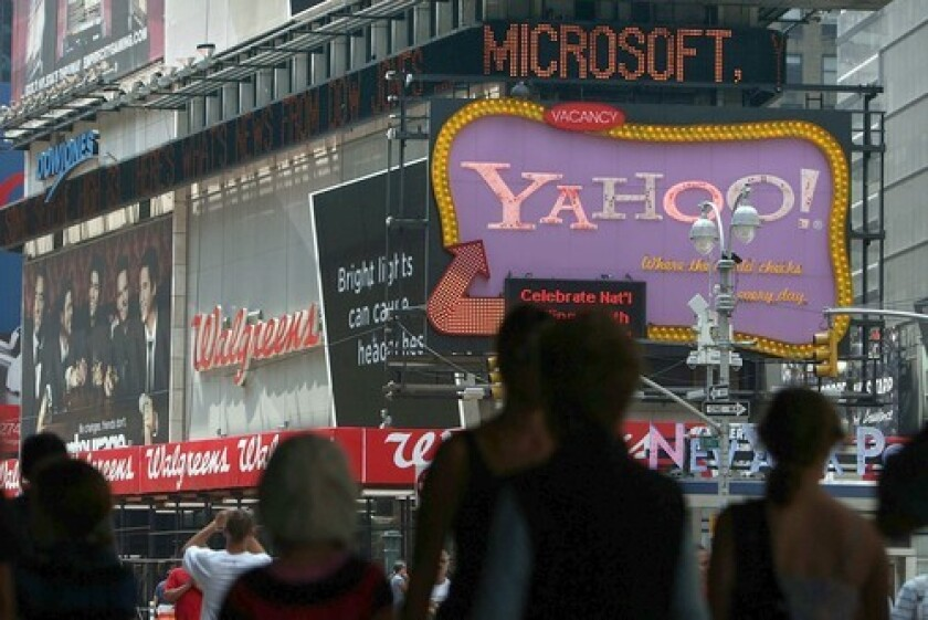 A Yahoo sign in New York's Times Square is topped by a news crawl announcing its search engine partnership with Microsoft.