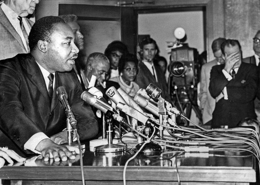 Aug. 19, 1965: The Rev. Martin Luther King Jr. answers questions during a news conference at Los Angeles City Hall. Mayor Samuel W. Yorty, right, listens with his hand covering his eyes.