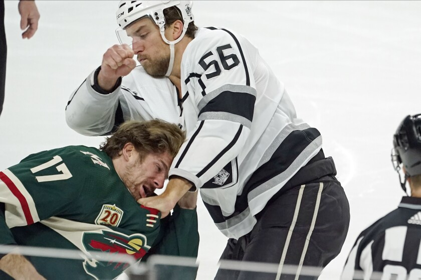 Minnesota Wild's Marcus Foligno, left, ducks away from a punch thrown by Kings' Kurtis MacDermid on Jan. 28