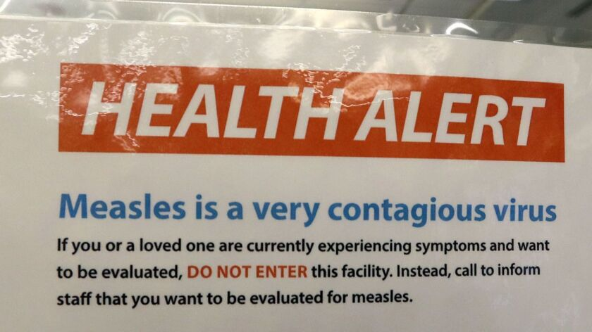 File - In this Feb. 13, 2019, file photo, a notice for a health alert about measles is posted on the