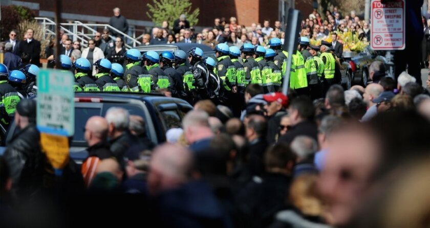 Police officers and others gather on Monday outside the funeral for 29-year-old Krystle Campbell, one of three people killed in the Boston Marathon bombings, in Medford, Mass.