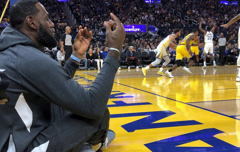 Lakers forward LeBron James sits along the baseline, appearing to meditate, during the exhibition game against the Warriors on Friday.