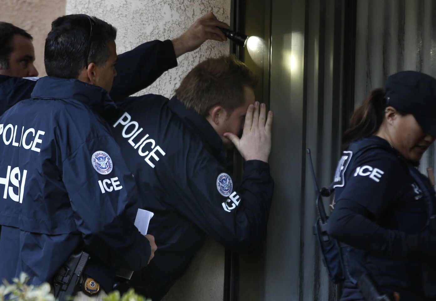 """ICE agents from the Department of Homeland Security look into the window of an apartment in Rowland Heights while executing search warrants during the ongoing investigation of """"birth tourism"""" centers."""