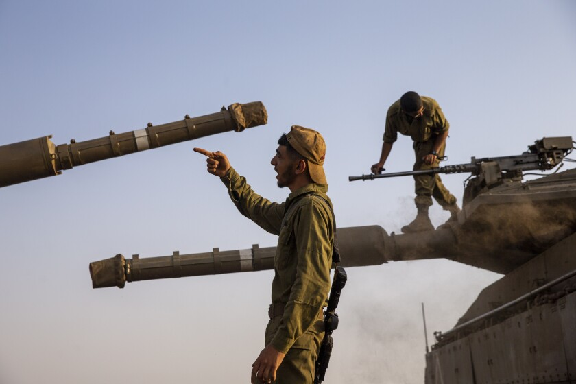 """Israeli soldiers work on tanks in the Israeli controlled Golan Heights near the border with Syria, not far from Lebanon border, Tuesday, July 28, 2020. Lebanon's prime minister has accused Israel of provoking a """"dangerous escalation"""" along the border in an attempt to modify the mandate of a U.N. peacekeeping force in south Lebanon. (AP Photo/Ariel Schalit)"""