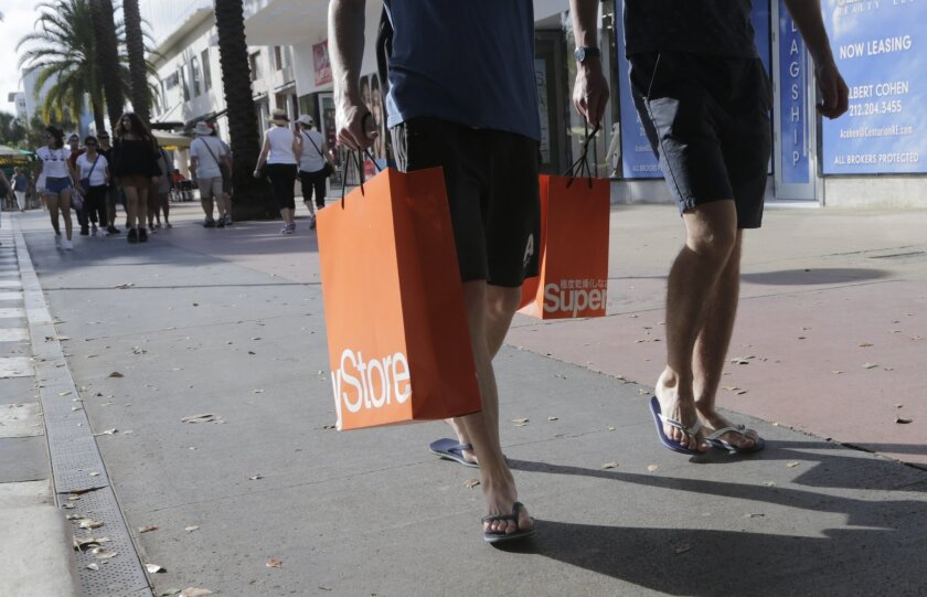 In this Wednesday, Feb. 3, 2016, photo, shoppers walk along Lincoln Road Mall, a pedestrian area featuring retail shops and restaurants in Miami Beach, Fla. On Friday, Feb. 19, 2016, the Labor Department reports on consumer prices for January. (AP Photo/Lynne Sladky)