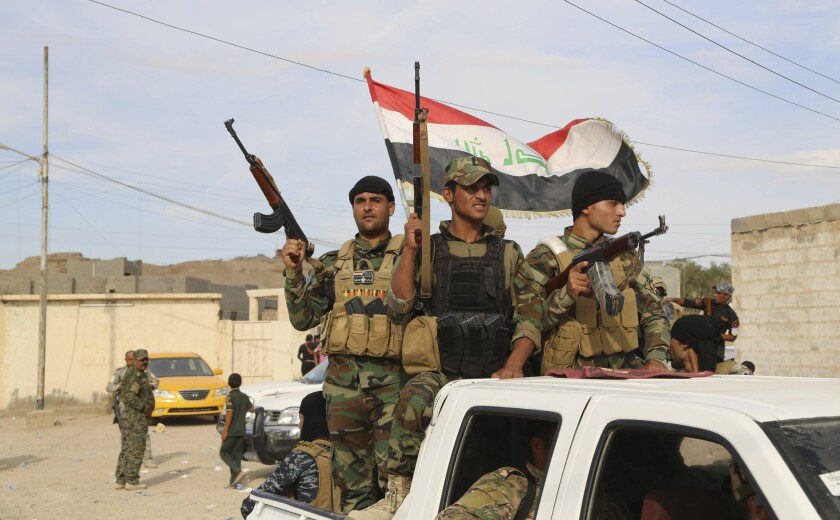 Sunni volunteer fighters parade through Khalidiya, located 60 miles west of Baghdad, as they prepare to support Iraqi security forces in liberating the city of Ramadi from Islamic State group militants on Oct. 10.