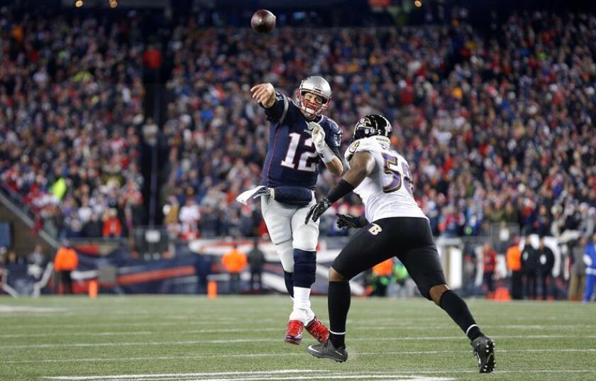 Tom Brady (i) de New England Patriots realiza un pase ante Elvis Dumervil (d) de los Baltimore Ravens durante un juego de la NFL en el estadio Gillette en Foxborough (EE.UU.). EFE/Archivo