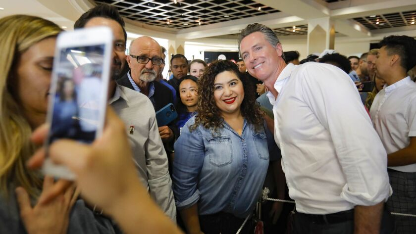 Gavin Newsom, Democratic candidate for California governor poses for a photo with a supporter during a campaign stop at San Diego State University on Friday.
