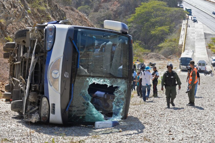 People remain near an overturned bus -which transported Argentinian football team Huracan's players- after an accident at the Caracas-La Guaira highway in Caracas on February 10, 2016. Huracan's coach and five players were injured on Wednesday after the bus taking them to Simon Bolivar International Airport overturned, a day after their Copa Libertadores football match against Caracas FC. AFP PHOTO / FEDERICO PARRAFEDERICO PARRA/AFP/Getty Images ** OUTS - ELSENT, FPG, CM - OUTS * NM, PH, VA if sourced by CT, LA or MoD **