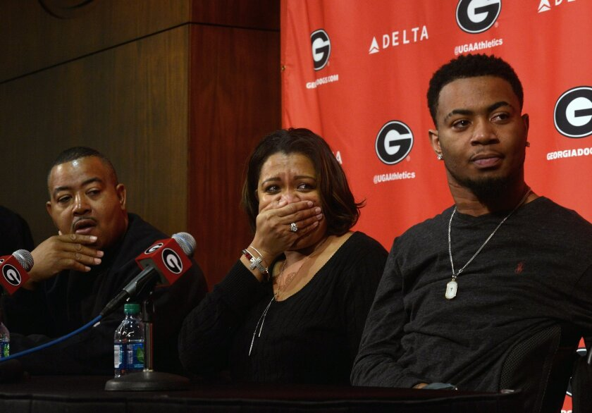Southern University football player Devon Gales, and his parents Tanisha, center, and Donny, left, react when it was announced funds were being raised for a new home accessible to his wheelchair, during a press conference in Athlens, Ga., Thursday, Feb. 25, 2016. Devon Gales suffered a paralyzing neck injury during a September football game at Georgia. (Richard Hamm/Athens Banner-Herald via AP) MAGS OUT; MANDATORY CREDIT