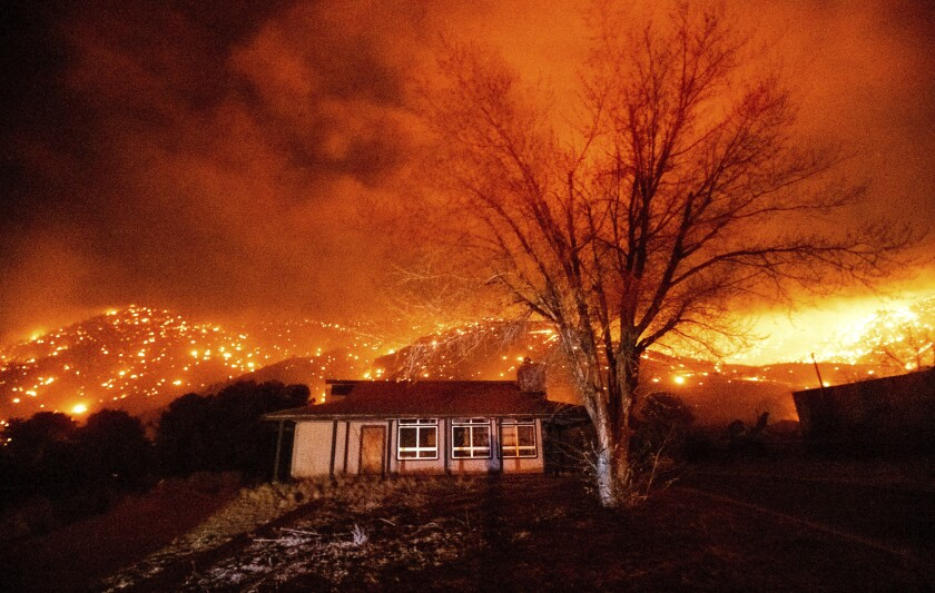 A home is surrounded by flames and embers in Mono County last year