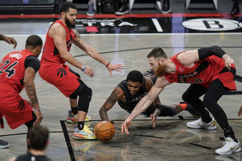 Brooklyn Nets' Kyrie Irving, center, fights for control of the ball with Toronto Raptors' Aron Baynes (46) and Fred VanVleet (23) during the second half of an NBA basketball game Friday, Feb. 5, 2021, in New York. (AP Photo/Frank Franklin II)
