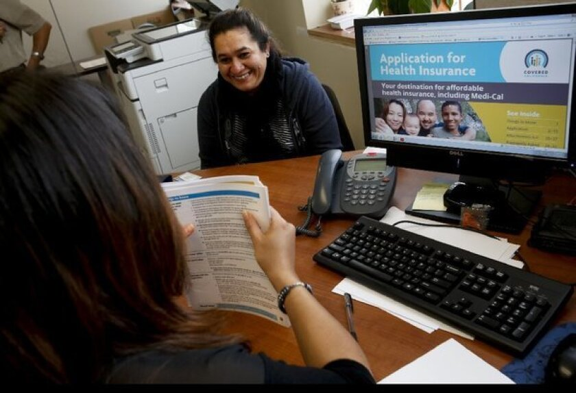Marta Viera smiles as she finishes her health insurance application under the Affordable Care Act with an enrollment counselor at a Los Angeles clinic last month.