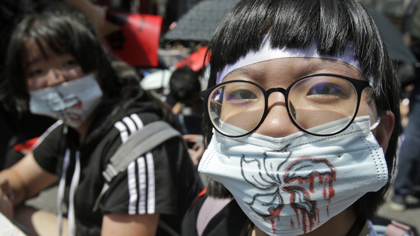 Hong Kong protest supporters in Taipei, Taiwan, wear masks depicting bloody flowers.
