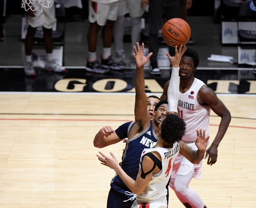 SDSU's Trey Pulliam (4) shoots and scores over Nevada's Desmond Cambridge Jr. (4) at the buzzer to give Aztecs the win.