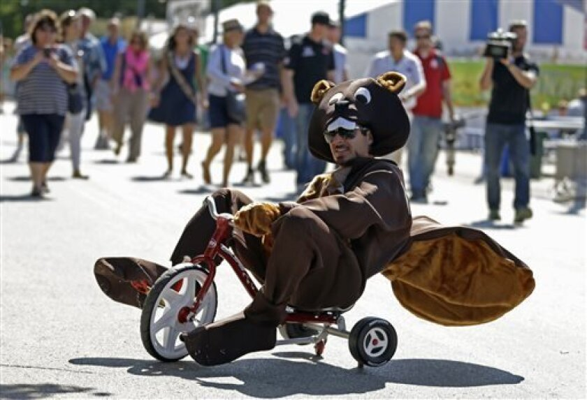 IndyCar Series driver Alex Tagliani, of Canada, rides a tricycle in a beaver costume at the Indiana State Fair in Indianapolis, Monday, Aug. 5, 2013 as part of the payoff of a charity fund-raising bet with fellow driver Scott Dixon. (AP Photo/Michael Conroy)