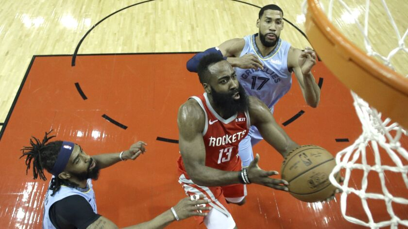 Houston Rockets' James Harden (13) goes up for a shot as Memphis Grizzlies' Garrett Temple (17) and Mike Conley defend.