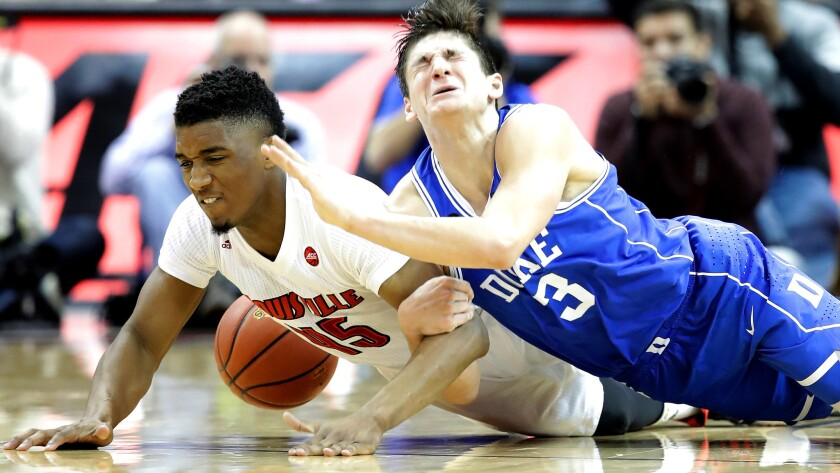 Louisville's Donvan Mitchell (45) and Duke's Grayson Allen (3) dive after a loose ball during their game Saturday.