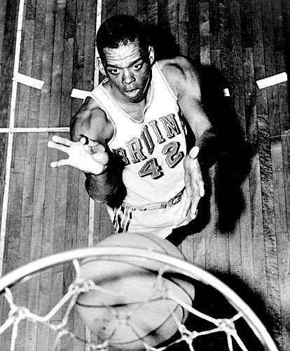 Walt Hazzard, a UCLA Bruins guard, is shown in an action pose under the net in 1962.