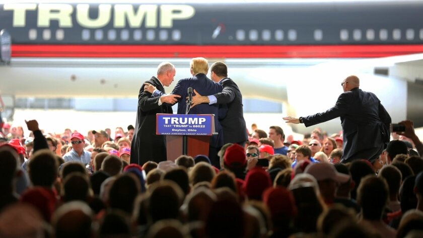 Security personnel surround Republican presidential candidate Donald Trump after a man tried to rush the stage during a campaign rally in Vandalia, Ohio, outside of Dayton, on Saturday, March 12, 2016. The man was stopped and Trump continued with his speech. (Carrie Cochran/The Cincinnati Enquirer