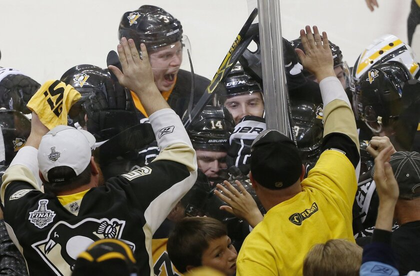 Pittsburgh Penguins' Conor Sheary is mobbed by teammates after his goal against the San Jose Sharks during overtime in Game 2 of the NHL hockey Stanley Cup Finals on Wednesday, June 1, 2016, in Pittsburgh. The Penguins won 2-1 to take a 2-0 series lead. (AP Photo/Gene J. Puskar)