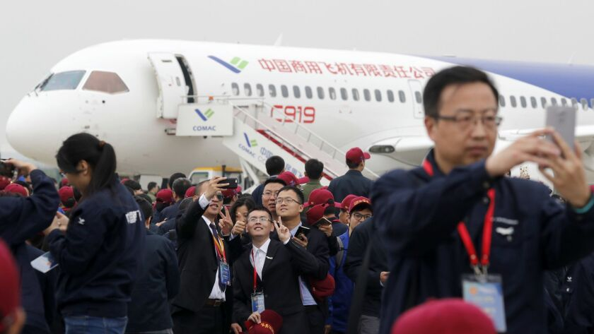 Attendees take photos in front of a Chinese C919 passenger jet after its first flight at Pudong Inte