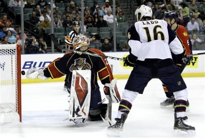 The puck gets past Florida Panthers goalie Tomas Vokoun, left, in the first period during an NHL hockey game in Sunrise, Fla., Wednesday, Jan. 5, 2011. Atlanta Thrashers' Andrew Ladd (16) had an assist on the goal. (AP Photo/Lynne Sladky)
