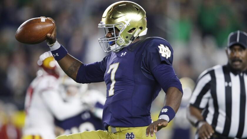 Notre Dame quarterback Brandon Wimbush high-steps into the end zone on a seven-yard run against USC on Saturday.