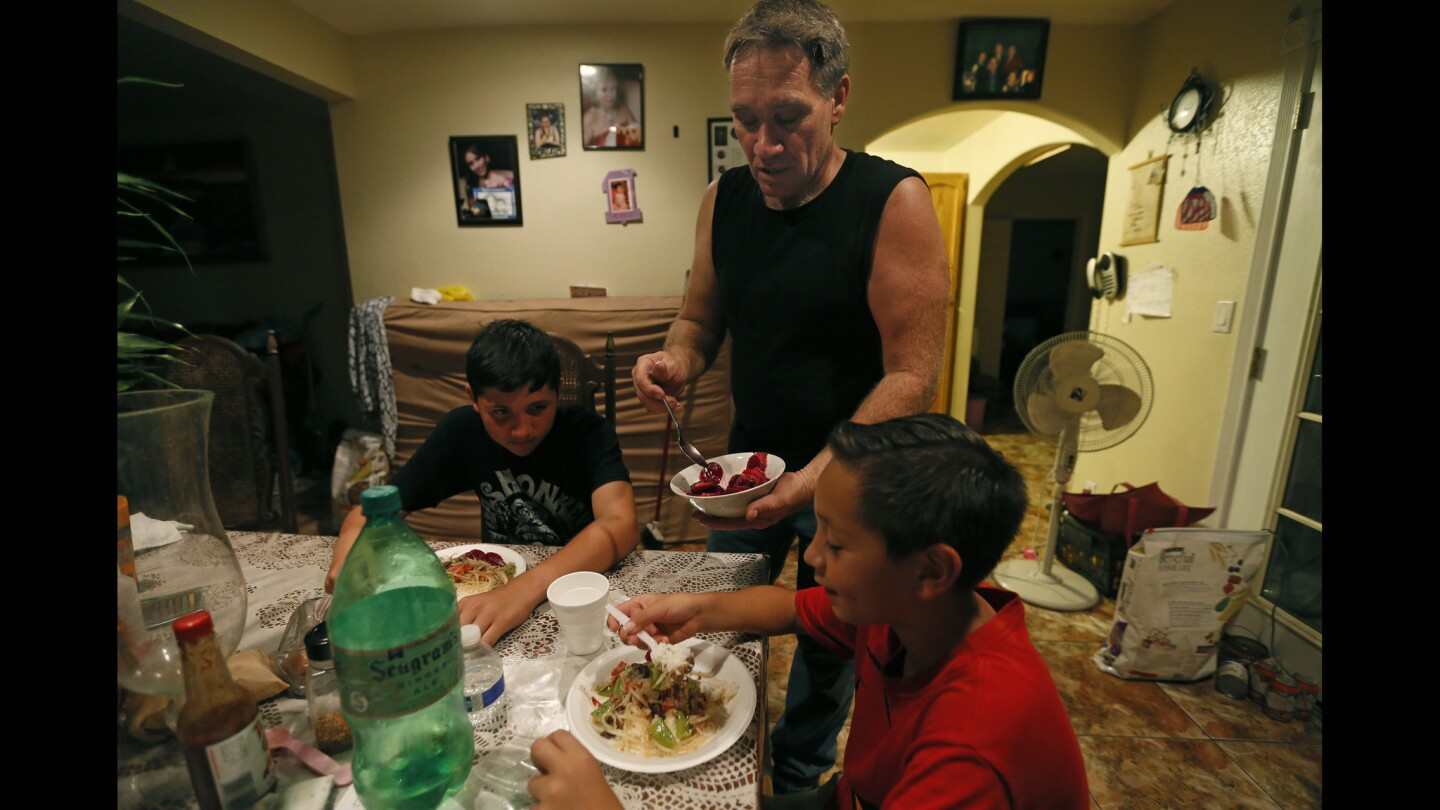 Michael Paulsen serves dinner to his sons Ryan, 12, and Brannon, 9, at their home in Vista, Calif. The automobile mechanic has been a single dad for nine years since his wife, a Mexican immigrant in the U.S. illegally, was deported.