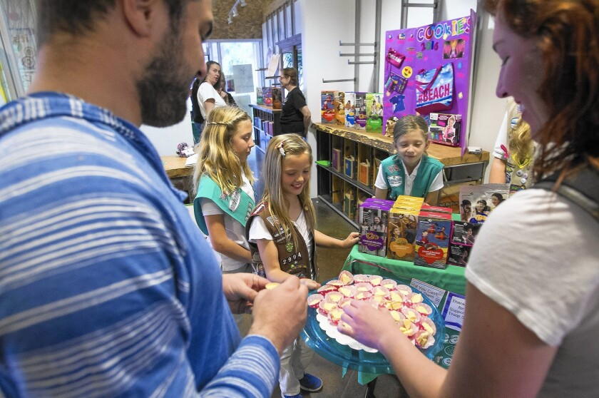Kelly Richards, 9, center, with Taylor Mahan, 11, and Isabella Zuniga, 9, offers a sample to Michael Frank, left, and Kristi Drake while selling Girl Scout cookies at The OC Mix on Wednesday.