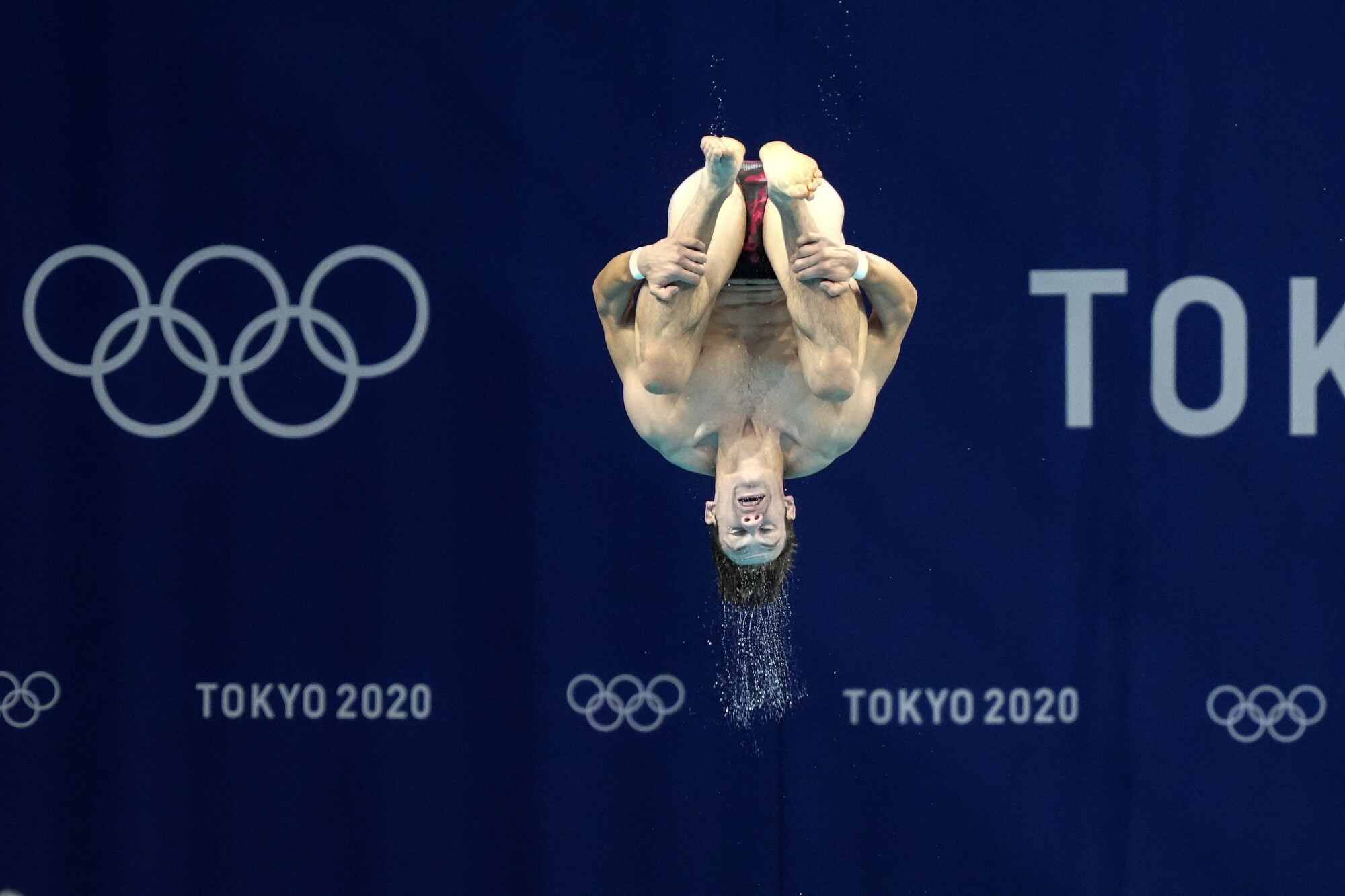 A diver jumps in front of the Olympic rings during a practice session in Tokyo.