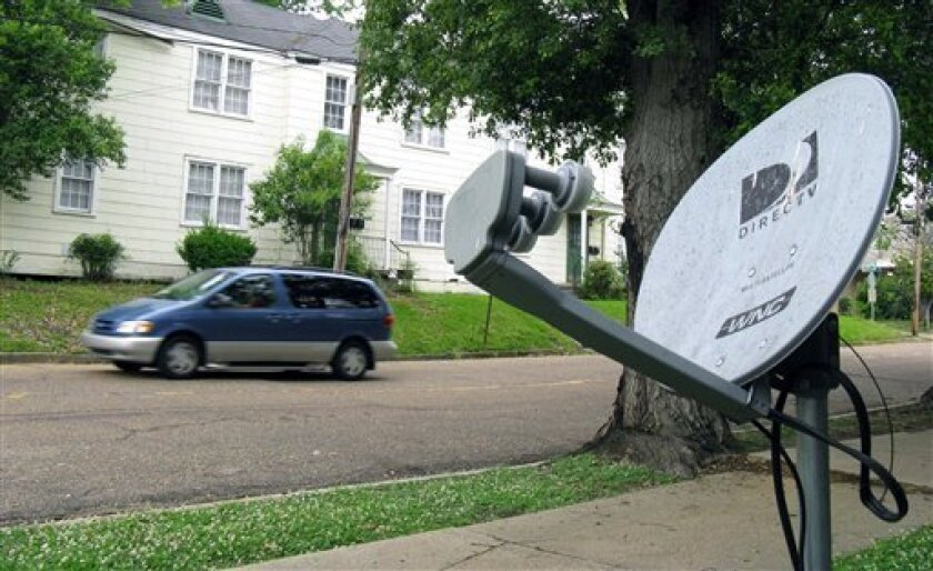 In this May 11, 2009 photo, a mini-van passes a DirecTV satellite dish in a residential area adjoining downtown Jackson, Miss. Tribune Broadcasting says there's been no settlement with DirecTV Inc. in their contract negotiations, which means DirecTV subscribers in 19 U.S. markets will lose access t