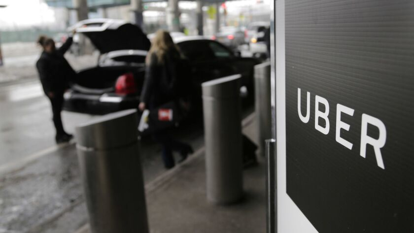 FILE - In this March 15, 2017, file photo, a sign marks a pick up point for the Uber car service at