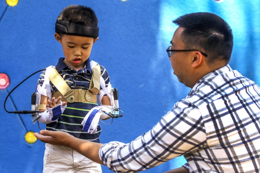 Five-year-old Max Ng, whose arms are paralyzed due to acute flaccid myelitis, is able to lift his hand and touch the hand of his father Ted Ng, thanks to a custom motorized orthotic brace that mechanical engineering undergraduate students at UC San Diego have created, during a demonstration of the brace at Rady Children's Hospital on Friday.