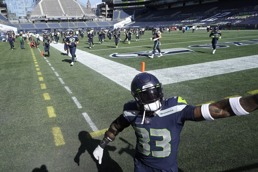 Seattle Seahawks strong safety Jamal Adams reaches up towards the stands as he heads to the locker room before an NFL football game against the Dallas Cowboys, Sunday, Sept. 27, 2020, in Seattle. (AP Photo/Elaine Thompson)