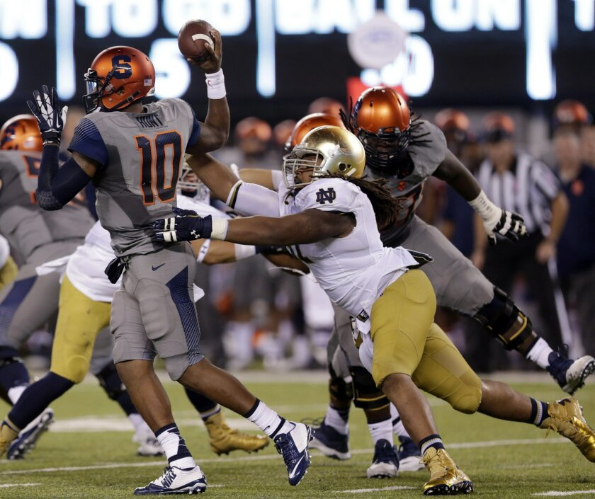 """FILE - In this Sept. 27, 2014, file photo, Notre Dame defensive lineman Sheldon Day, right, applies pressure on Syracuse quarterback Terrel Hunt (10) during the second half of an NCAA college football game in East Rutherford, N.J. Day doesn't want to be an """"almost guy."""" Day said that's the phrase defensive coordinator Brian VanGorder uses for players who get a quarterback pressure but don't get the sacks or almost tackles someone in the backfield. (AP Photo/Julio Cortez, File)"""