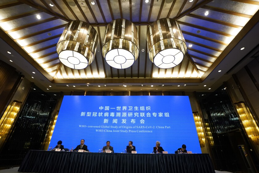 """Six people sit at a table in front of a screen that reads, in part, """"WHO-China joint study press conference."""""""