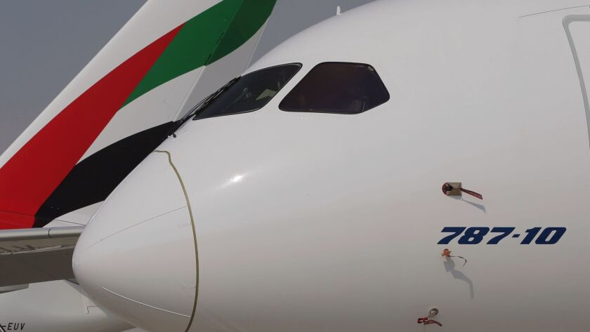 A Boeing 787-10 Dreamliner is parked in front of an Emirates Airline plane during the opening day of