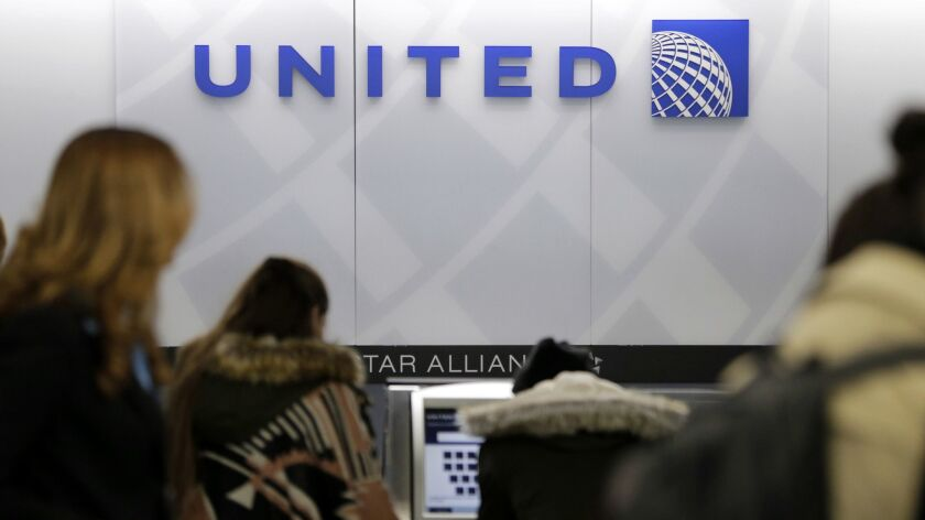 People stand in line at a United Airlines counter at LaGuardia Airport in New York. The airline announced a higher spending minimum to qualify for Premier 1K status on its MileagePlus loyalty reward program.