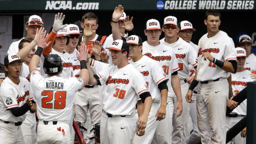 Oregon State's Kyle Nobach (28) is greeted at the dugout after he scored against Mississippi State on a one-run single by Michael Gretler in the second inning.