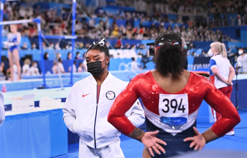 Simone Biles looks on after pulling out of the women's team final