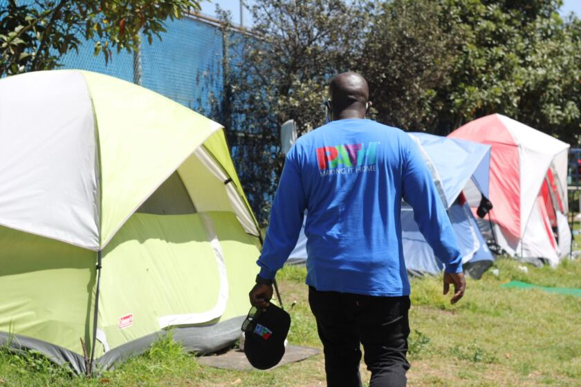 A PATH Outreach Specialist approaches tents in a park encampment.