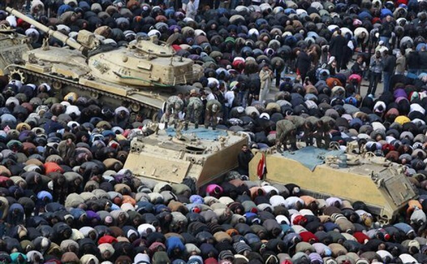 Anti-government protesters, and Egyptian soldiers on top of their vehicles, make traditional Muslim Friday prayers at the continuing demonstration in Tahrir Square in downtown Cairo, Egypt Friday, Feb. 11, 2011. (AP Photo/Ben Curtis)