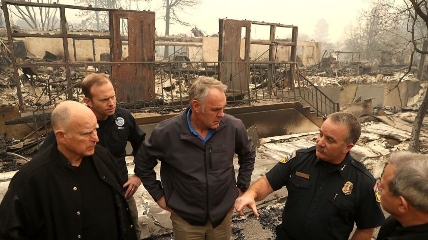 FEMA Administrator Brock Long, second from left, joins Gov. Jerry Brown and others in November to tour a school burned by the Camp Fire in Paradise.