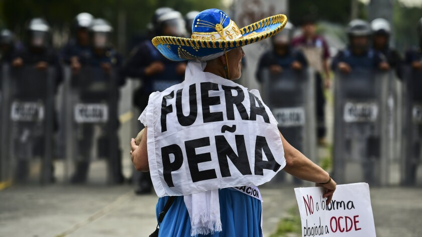 """A teacher protesting a government education reform plan wears a sign saying """"Out with Peña,"""" a reference to the Mexican president."""