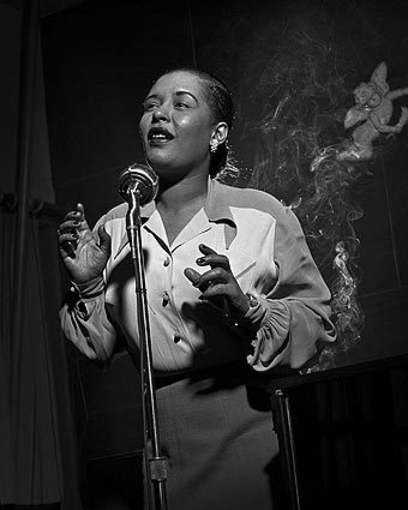 Billie Holiday performs at a microphone in New York.