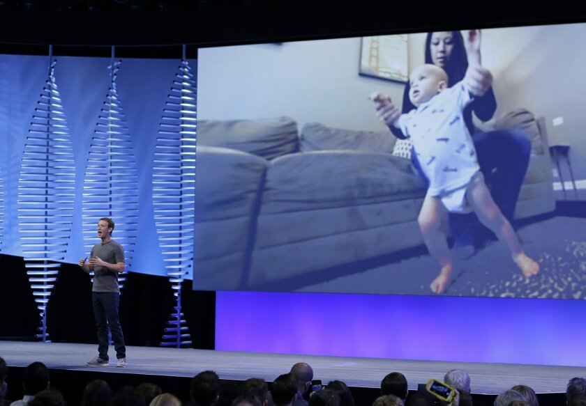 """Facebook CEO Mark Zuckerberg delivers the keynote address with a video image of his wife, Priscilla Chan, and daughter, Max, behind him at the F8 Facebook Developer Conference Tuesday, April 12, 2016, in San Francisco. Zuckerberg said Facebook is releasing new tools that businesses can use to build """"chatbots,"""" or programs that can talk to customers in conversational language. (AP Photo/Eric Risberg)"""