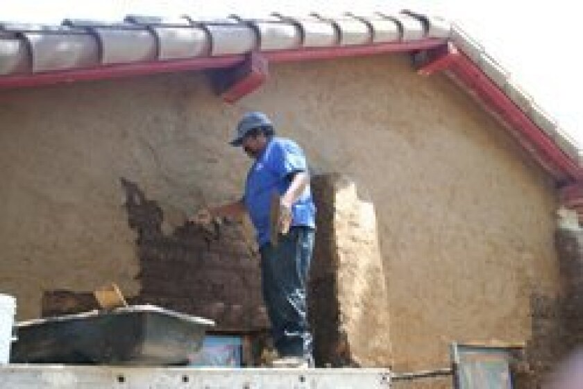 A clay and straw coating being applied to the north side. Photo/Karen Billing