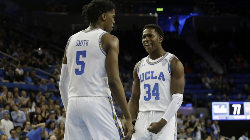 UCLA guard Chris Smith celebrates with teammate David Singleton (34) after scoring against St. Francis during the second half of their game Friday.